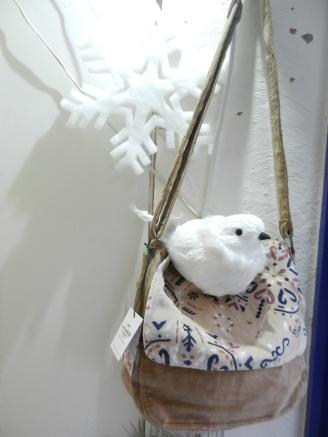 oiseau blanc posé sur un sac besace en velours.Noël 2017